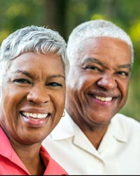 Mature African American couple looking at the camera smiling.